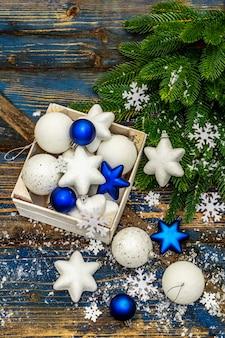 Weiße und blaue weihnachtskugeln und sterne, tannenzweige und schneeflocken. draufsicht