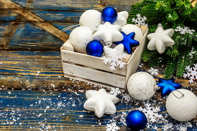 Weiße und blaue weihnachtskugeln und sterne, tannenzweige und schneeflocken. speicherplatz kopieren
