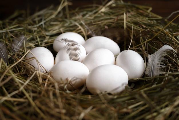 Weiße und braune eier auf stroh und hölzernem dunklem hintergrund.