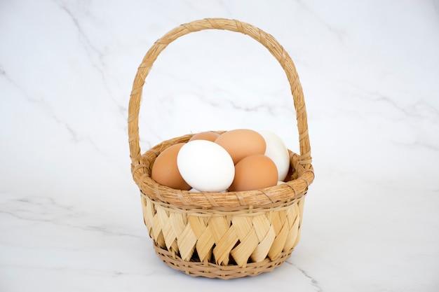 Weiße und braune eier im weidenkorb auf marmorhintergrund. frische bauernhühnereier. frohe ostern.