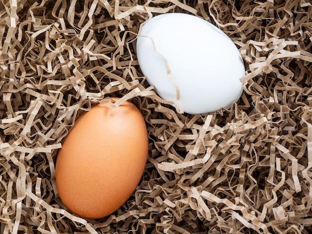 Weiße und braune hühnereier sind in weicher, stoßfester papierverpackung, nahaufnahme, modell. konzept: sorgfältige lagerung und lieferung zerbrechlicher waren. eier zum malen und dekorieren zu ostern vorbereiten.