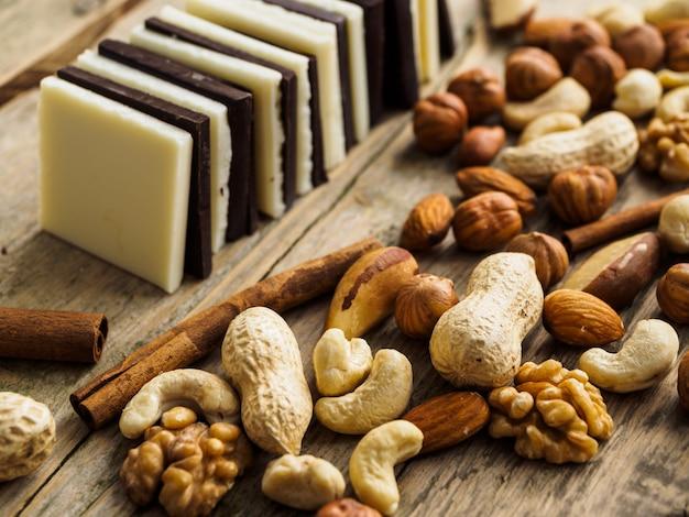 Weiße und dunkle schokolade reihte sich auf einer holzoberfläche ein. viele nüsse, rosinen und zimt