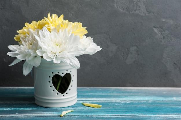 Weiße und gelbe chrysantheme in einem topf