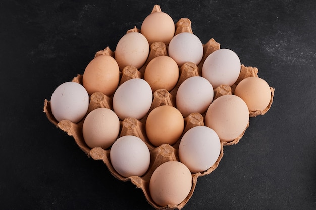 Weiße und gelbe eier in einem pappbehälter.
