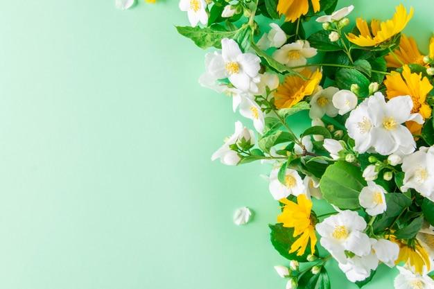 Weiße und gelbe frühlingsblumen auf einem grünen hintergrund mit kopienraum.
