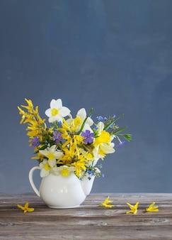 Weiße und gelbe frühlingsblumen in teekanne auf holztisch auf blauem hintergrund
