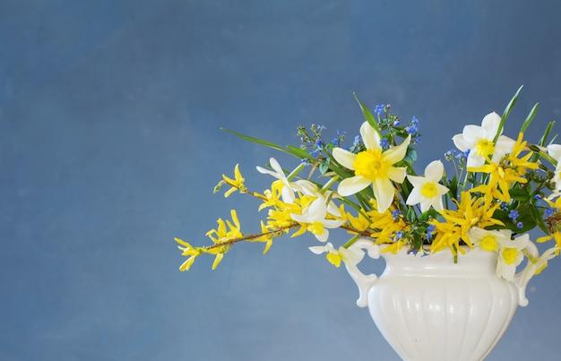 Weiße und gelbe frühlingsblumen in vase auf holztisch auf blauem hintergrund