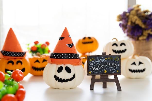 Weiße und gelbe geistkürbise mit hexenhut und glücklicher halloween-text