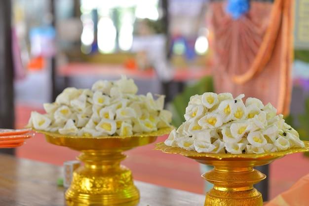 Weiße und gelbe sandelholzblumen oder künstliche blumen für beerdigung.
