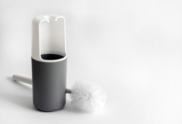Weiße und graue kunststoff-toilettenbürste auf weißer oberfläche mit kopierraum