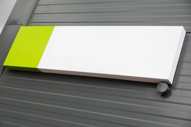 Weiße und grüne rechte winklige leere tablette, die an der wellblechwand hängt
