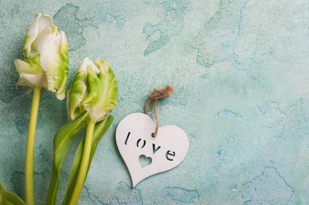 Weiße und grüne tulpenpaare mit hölzernem herzen