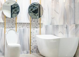 Weiße und hölzerne Badezimmerecke mit weißer Badewanne, Toilette und eingebautem Regal