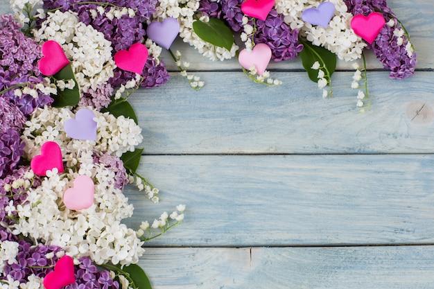 Weiße und lila flieder, maiglöckchen und bunte herzen aus satin