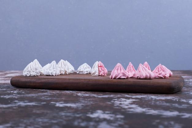 Weiße und rosa blütenförmige marshmallows auf einer holzplatte auf blau.