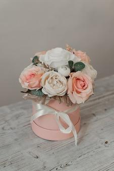 Weiße und rosa blumen in einer geschenkbox. dekorative blumen. künstliche blumen in einer runden schachtel.