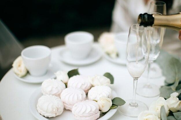 Weiße und rosa marshmallows und champagner auf dem hochzeitstisch. festliches abendessen