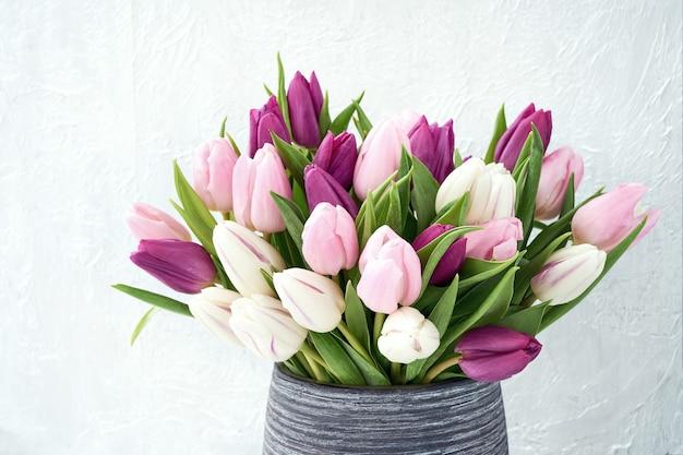 Weiße und rosa tulpen in der vase. urlaubshintergrund, kopierraum