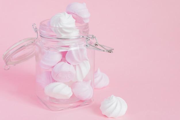 Weiße und rosa verdrehte meringen in einem glasgefäß auf rosa hintergrund