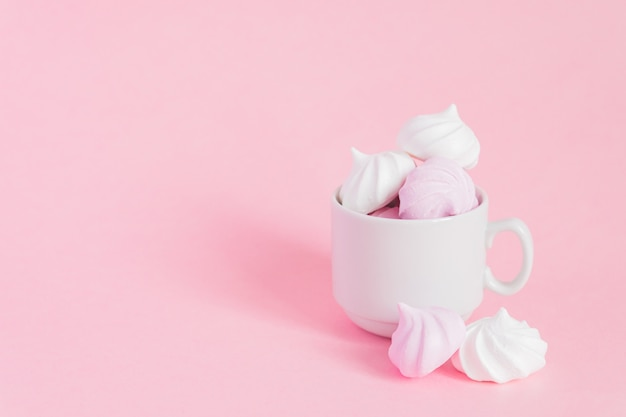 Weiße und rosa verdrehte meringen in einer kleinen porzellankaffeetasse auf rosa backgroundwith kopienraum