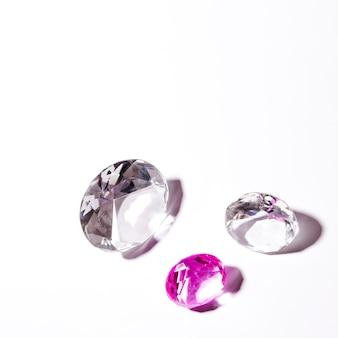 Weiße und rosafarbene transparente diamanten auf weißem hintergrund
