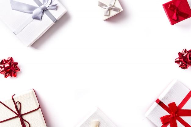 Weiße und rote geschenkboxen lokalisiert auf weißer draufsicht, copyspace.