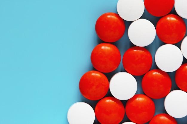 Weiße und rote medikationspillen auf blau