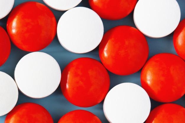 Weiße und rote medikationspillen auf blauer oberfläche