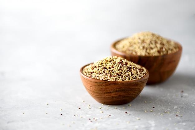 Weiße und rote rohe organische quinoa in der hölzernen schüssel und im rosmarin. gesunde lebensmittelzutaten.