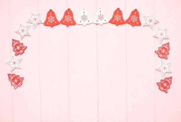 Weiße und rote sterne und weihnachtsbäume rahmen auf rosa holzoberfläche ein