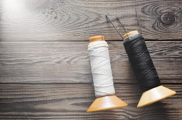 Weiße und schwarze garnrollen mit nadeln auf rustikalem holz.