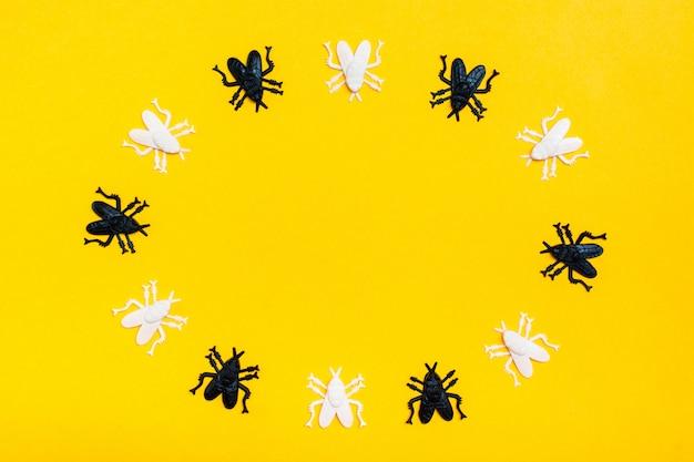 Weiße und schwarze plastikfliegen liegen in einem kreis auf einem gelben rahmenpapphintergrund. bereite halloween-einladung. kopieren sie platz