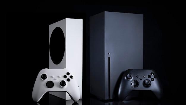 Weiße und schwarze spielkonsolen und controller mit schwarzem hintergrund