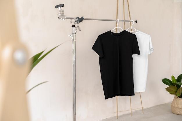 Weiße und schwarze t-shirts auf kleiderbügeln zur designpräsentation