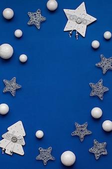 Weiße und silberne dekorationen flach auf klassischem blauem hintergrund mit kopierraum. weihnachtshintergrund in der farbe des jahres 2020 klassisch blau mit stilvollen weißen und silbernen ornamenten, draufsicht