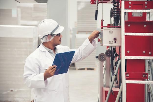 Weiße uniform des jungen mannes, die maschinenausrüstung für safty zuerst an der speicherfabrik überprüft