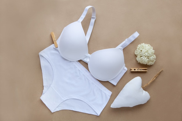 Weiße unterwäsche aus baumwolle. bio-wäsche-damenwäsche auf braunem hintergrund. ansicht von oben aus natürlichem weichem stoff