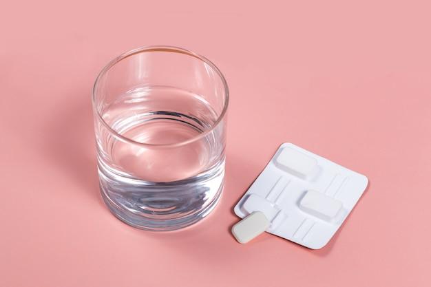 Weiße vaginale antibakterielle pillen auf rosa hintergrund kerzen werden im wasser eingeweicht und in vagina eingespritzt, um candidiasis, drossel, entzündung zu behandeln. wirksames modernes medikament zur behandlung von krankheiten