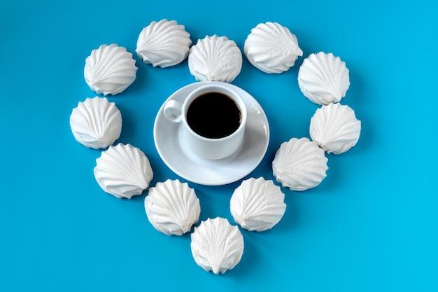 Weiße vanille-marshmallows auf blauem grund in form von herzen