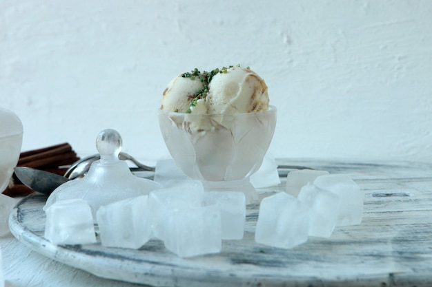 Weiße vanilleeiskugeln in schüssel mit nüssen und eiswürfeln und großem zimt. weißer hintergrund