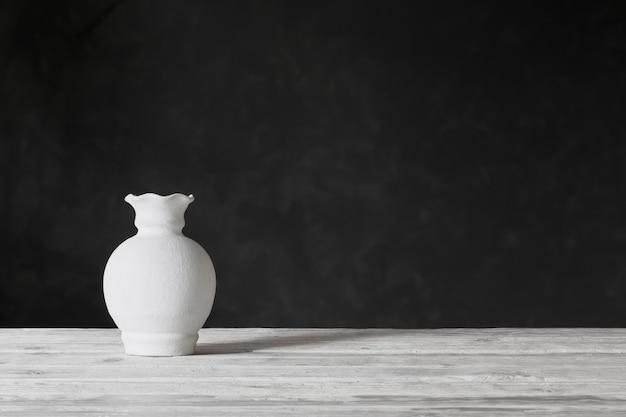 Weiße vase auf holztisch auf schwarzem hintergrund