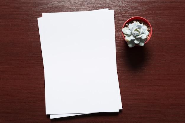 Weiße visitenkarte auf holztisch. leeres porträt a4.