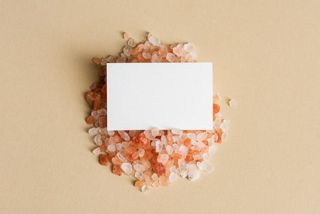 Weiße visitenkarte auf orangefarbenen kieselsteinen