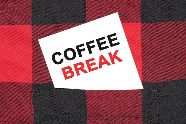 Weiße visitenkarte mit text-kaffeepause liegt im ärmel eines karierten hemdes.