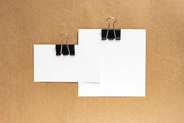 Weiße visitenkarten kombiniert mit einer schwarzen büroklammer auf kraftpapierhintergrund. ansicht von oben