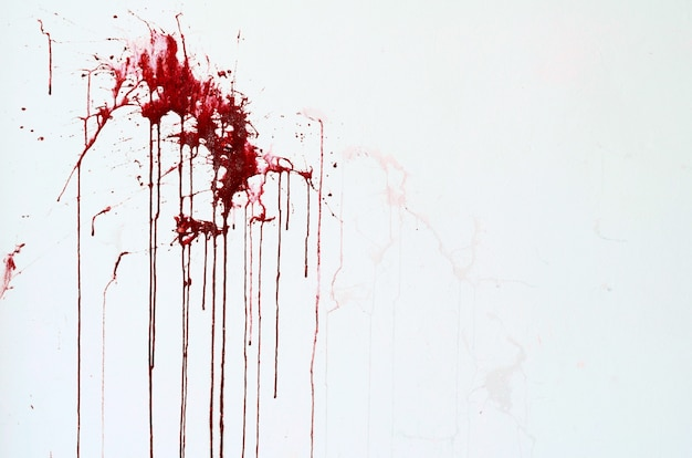 Weiße wand des hintergrundbeschaffenheitszements mit roten blutartigen farbenstreifen