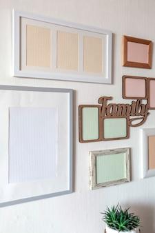 Weiße wand mit einem satz verschiedener leerer vertikaler und horizontaler bilderrahmen, um eine familienfotogalerie an der wand zu erstellen, um einen moment festzuhalten, modellvorlage an der weißen wand, lebensstil