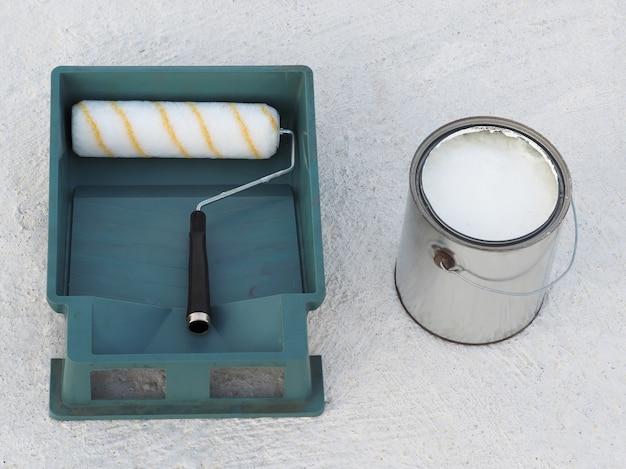 Weiße wasserfeste farbe im eimer mit grünem behälter und walze auf dem dach.