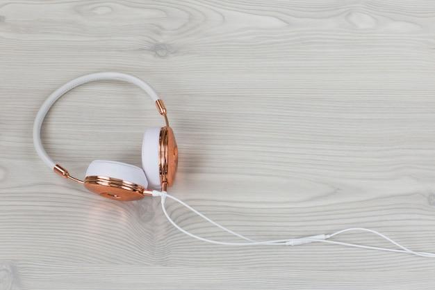 Weiße weibliche kopfhörer auf einem hellen hintergrund und einem freien platz für text