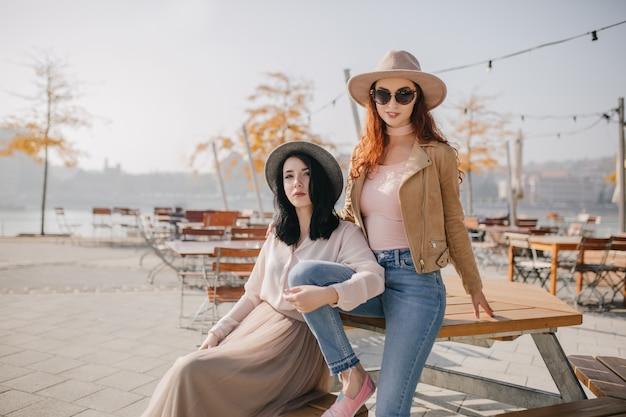 Weiße weibliche modelle, die guten tag im herbstpark genießen